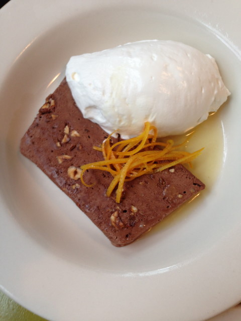 Frozen chocolate-hazelnut therrine with whipped cream and candied orange peel.