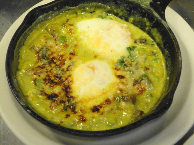 Two eggs broiled in  a skillet with watercress, spring peas, mushrooms, watercress cream and parmesan.