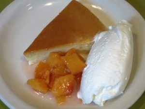 U Pastizza, Corsican pudding cake scented with lemon and vanilla, served with peach compote and whipped cream