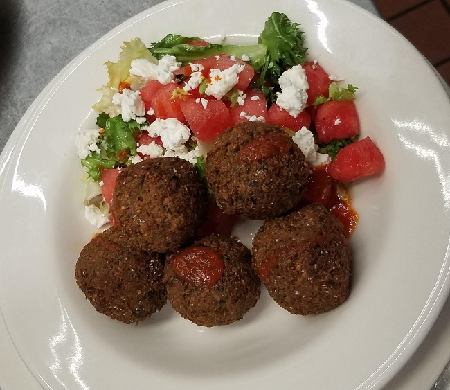 Crispy chickpea falafel served on a salad of watermelon, curly endive, feta cheese and lime vinaigrette, topped with our house-made harissa