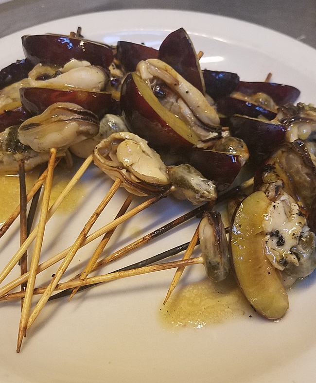 Grilled skewers of house smoked mussels and Italian plums marinated with sherry