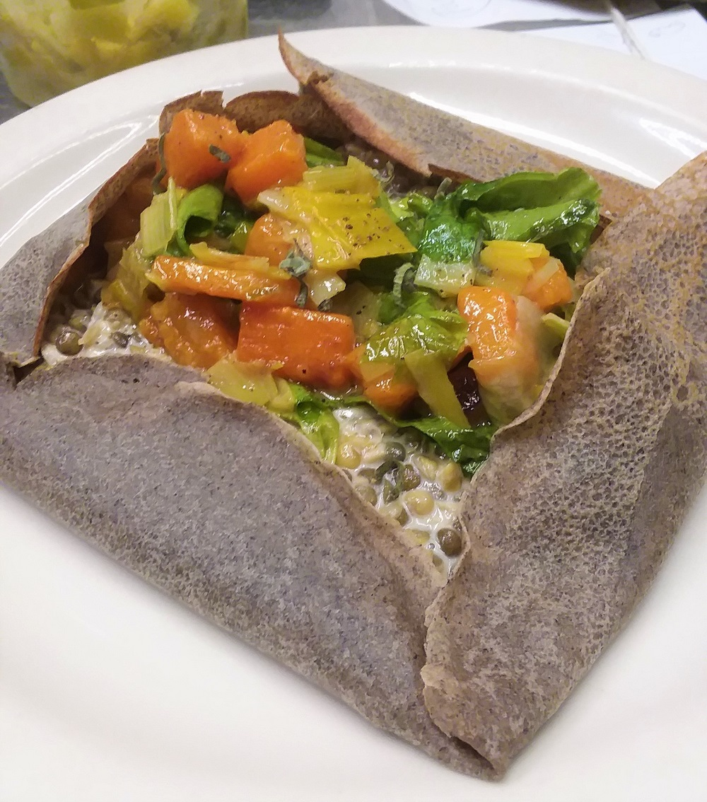 Buckwheat crepe filled with lentils simmered with cream and white wine, topped with a sauté of leeks, escarole and butternut squash